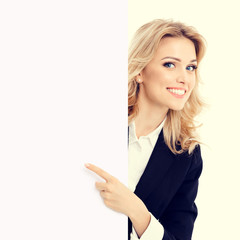 Portrait of happy smiling businesswoman in confident style black suit, showing blank signboard with copy space for slogan or advertise text. Brunette model in business success concept shot.