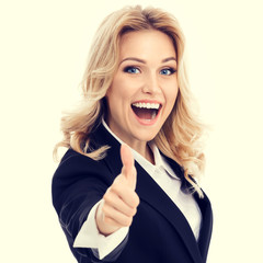 Happy smiling young businesswoman in confident style black suit, showing thumbs up gesture. Caucasian blond model in business success concept.