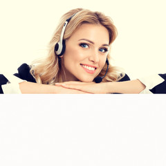 Call center. Customer service operator in confident style black suit and headset showing signboard with copy space area for text or advertise slogan. Caucasian blond model in business success concept.