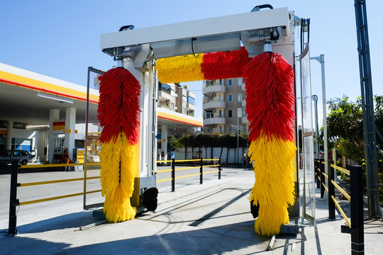 Empty outdoor self service car wash at gas station premises. Colorful red and yellow rotating carwash brushes. Close up, copy space, background.