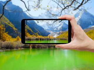 Hand holding black smartphone take a photo of Pearl Lake or Zhuoma La Lake and snow mountain
