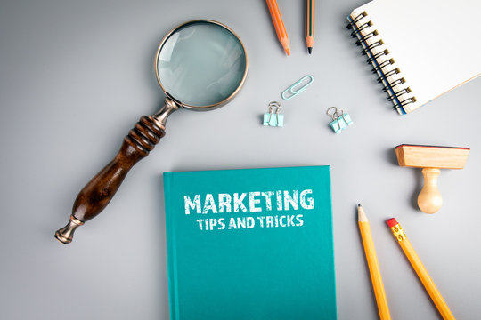 Marketing, tips and tricks. Green book cover and magnifying glass