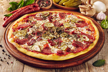 Meat and vegetable pizza on wooden table close up