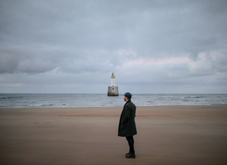 Man standing on beach and looking at the sea