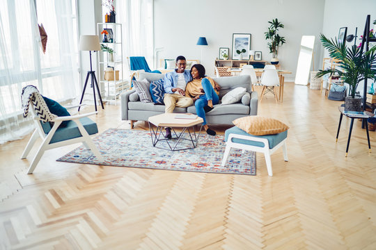 Happy african american young family sitting on sofa in modern designer living room in apartment, positive dark skinned marriage spending time together at home with stylish furniture and decoration.