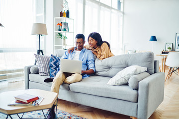 Positive african american woman watching video on laptop computer with boyfriend spending free time at home, dark skinned couple in love making online shopping together on netbook in living room.