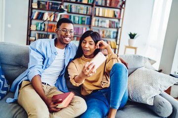Happy african american hipster girl having fun with her boyfriend at home interior posing for selfie on mobile phone camera, smiling dark skinned couple in love using smartphone for making photo