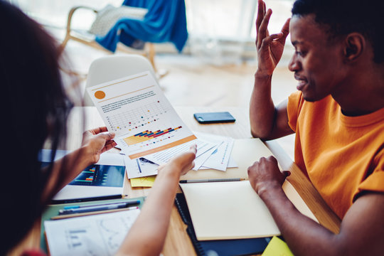 Cropped view of African American colleagues brainstorming on accounting report sitting at desktop with stationery, dark skinned man studying with tutor holding graphs with infographic statistics