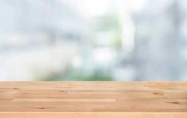 Selective focus of wood table top on white wall glass (big window) background