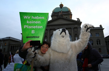A woman takes a selfie with a person dressed as a polar bear before members of the Swiss Glaciers Initiative committee hand over boxes with signatures supporting a referendum at the Federal Chancellery in Bern