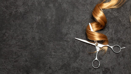 Foto op Textielframe Kapsalon The hairdresser. Scissors and curl of hair on a black background