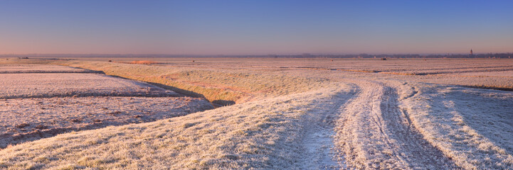 Fototapete - Dike through Dutch landscape in winter at sunrise