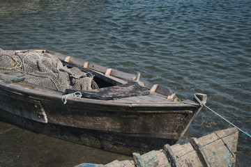 Old wooden rowboat with fishing net in port.