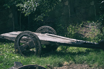 Historic ancient wooden wagon on meadow near forest.