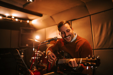 Portrait of a cheerful singing man with a guitar in the studio.