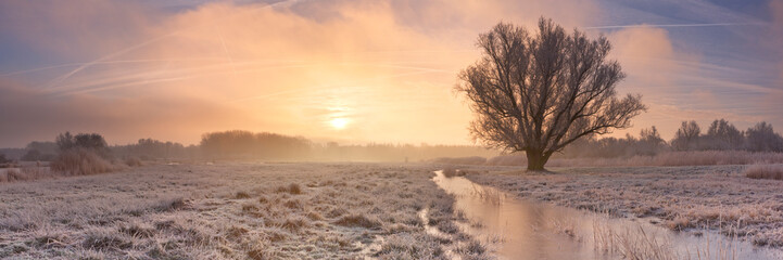 Sunrise over a frozen landscape in The Netherlands
