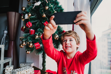 portrait of beautiful kid boy at home by the christmas tree and using mobile phone to take a selfie