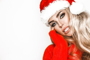 Beauty Christmas fashion model girl . Long straight blonde hair in red santa hat. Sexy blonde young woman portrait, fashionable party clothes and accessories - Image