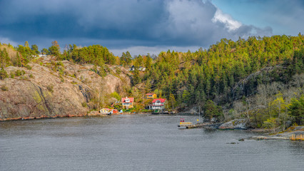 Quiet cove with picturesque summer houses in Stockholm Archipelago in Baltic sea at spring sunny evening.