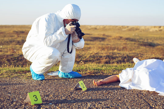 Detective studying a crime scene taking photographs.