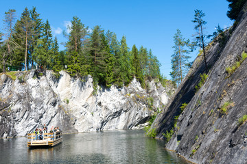 Boat with tourists on the lake in marble canyon in Ruskeala