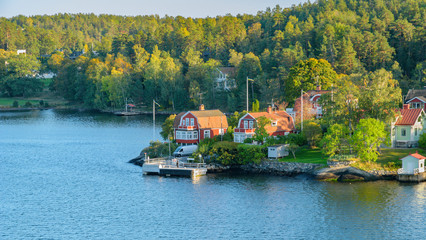 Rocky coast of Stockholm archipelago in Baltic sea with traditional white and red houses at sunny autumn evening with a fall scenery.