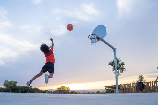 Boy throwing a ball in a basket on a basketball court