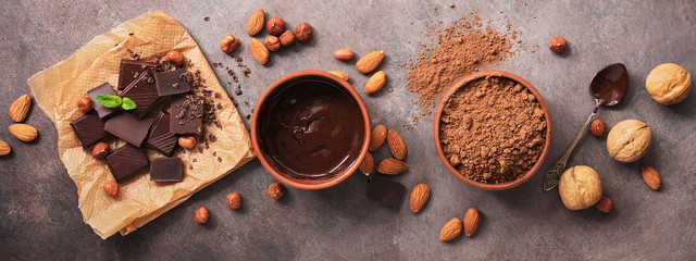 Border with chocolate, nuts and cocoa powder on a dark background. Overhead, flat lay