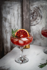 cocktail drink with blood orange and ice decorated with basil on white wooden stool