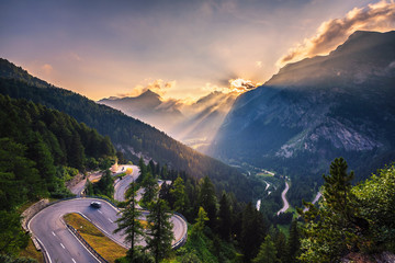 Spoed Fotobehang Bleke violet Maloja Pass road in Switzerland at sunset