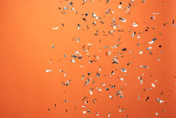 shiny silver confetti on orange background Fotobehang