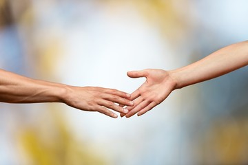 Hands reaching out and touching each other on a bokeh background
