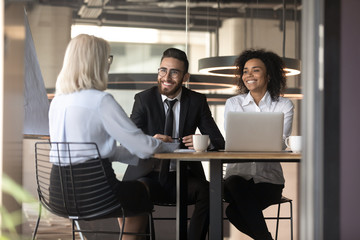 Smiling multiracial employers laugh talking with job candidate in office