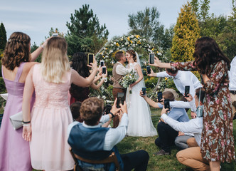 Friends of the newlyweds take pictures on the smartphone ceremony and hugs. Wedding portrait of the groom, bride and guests on the background of the arch on the nature in the park.