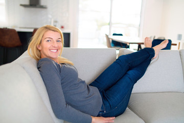 Relaxed woman enjoying rest on comfortable sofa, calm attractive girl relaxing on couch