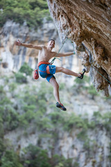Cheerful rock climber hanging on rope while climbing challenging route