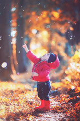 Little toddler boy in red rubber boots and red jacket catching drops of rain in autumn park. Orange forest leaves on background