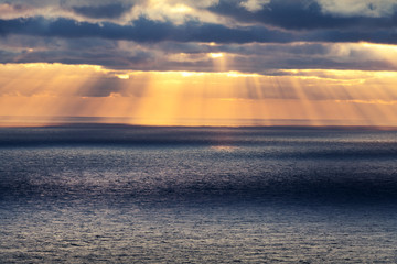 Sunset in the ocean with glowing sun rays and cloudy sky. Sea sunrise background. Landscape photography