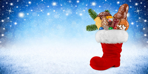 Red st nicholas day boot filled with chocolate santa claus cookies gingerbread cinnamon stars orange and green fresh fir branches blue white snow panorama background
