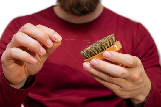 Man with beard pulls hair out beard brush, close-up of cleaning hair isolated on white