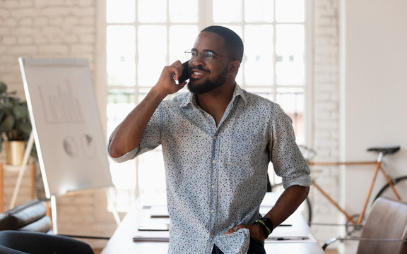 Successful millennial mixed race businessman holding mobile phone call.