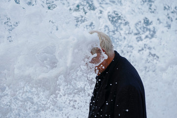 Dressed in a long wool trench coat Bruce Parker enjoys the waves spraying him as they crash on the beach during the arrival of a Winter storm in Oceanside