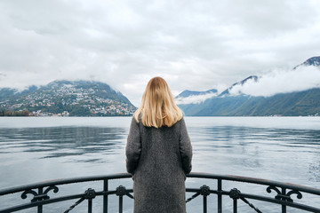Beautiful caucasian woman stands on pier in Lugano. Girl in travel. Lake Lugano, southern slope of Alps. Landscape in Switzerland. Amazing scenic outdoors view. Canton of Ticino. Adventure lifestyle