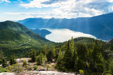 Majestic Howe Sound surrounded by towering forested mountains on a partly cloudy summer day. Squamish, BC, Canada.