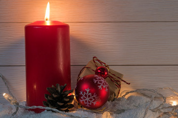 Red Christmas candle with lights and decorations on snow and wooden backgrouns. Selective focus and copy space.