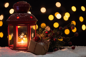 Lit Christmas lantern with a wrapped box and decorations on snow with blurred lights in background. Selective focus and copy space.