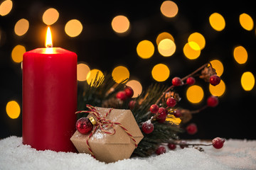 Christmas candle with a wrapped gift and decorations on snow with blurred light in background. Slective focus and copy space.