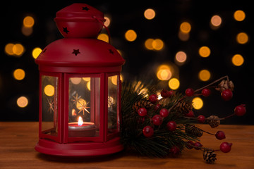 Close up of a lit red Christmas lantern and a pine brach on a wooden table with blurred lights in background. Slective focus and copy space.