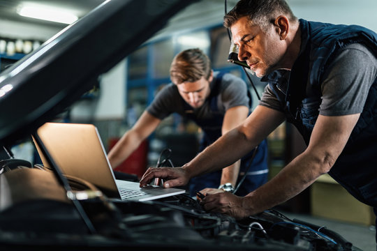 Auto mechanic using laptop while working on car diagnostic with his coworker.