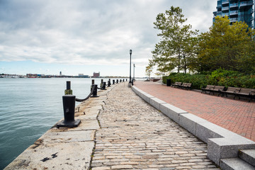 Deserted Cobblestone path running alongside a harbour on a cloudy autumn morning. Boston MA, USA.